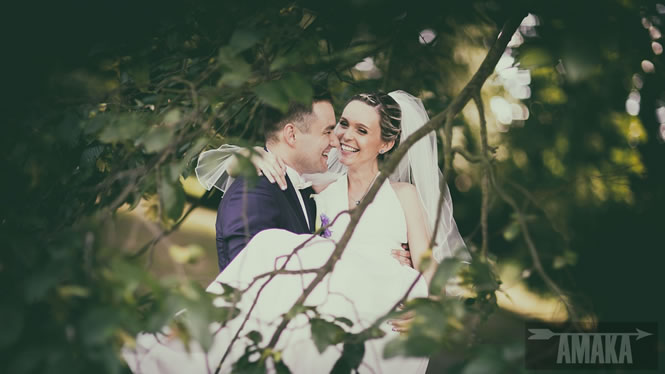 Šťastní novomanželé. Nevěsta je v náručí ženicha. Svatební focení, AMAKA tým.